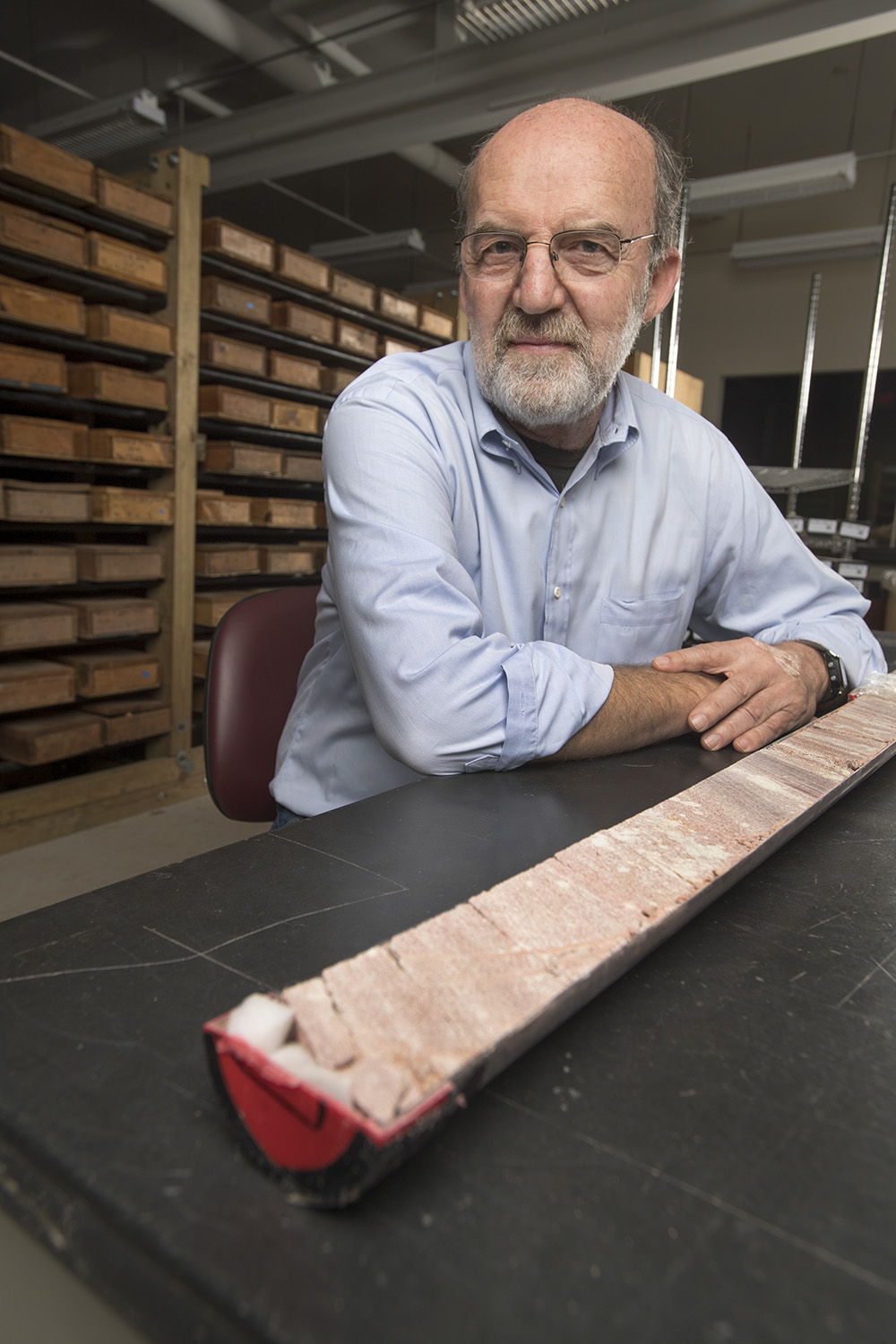 Rutgers University–New Brunswick Professor Dennis Kent with part of a 1,700-foot-long rock core through the Chinle Formation in Petrified Forest National Park in Arizona. The background includes boxed archives of cores from the Newark basin that were compared with the Arizona core. Photo Credit: Nick Romanenko/Rutgers University