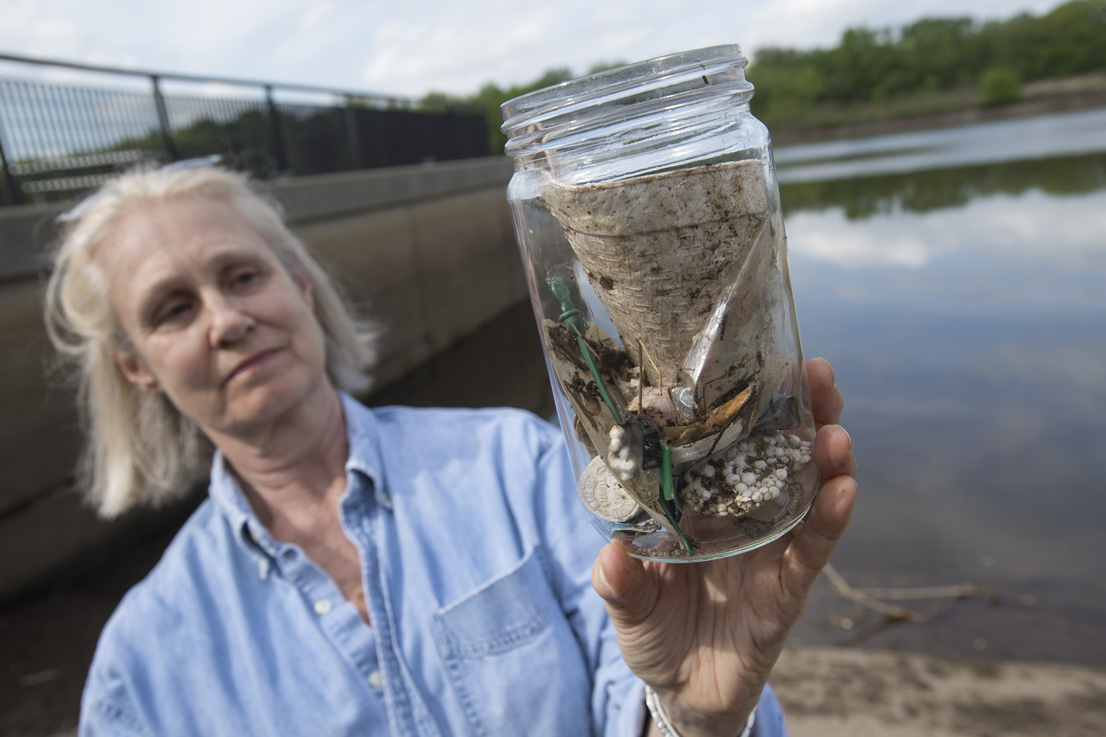 Beth Ravit, co-director of the Rutgers Center for Urban Environmental Sustainability, holds a jar filled with plastics collected along the Raritan River in New Brunswick, New Jersey. Photo: Nick Romanenko/Rutgers University