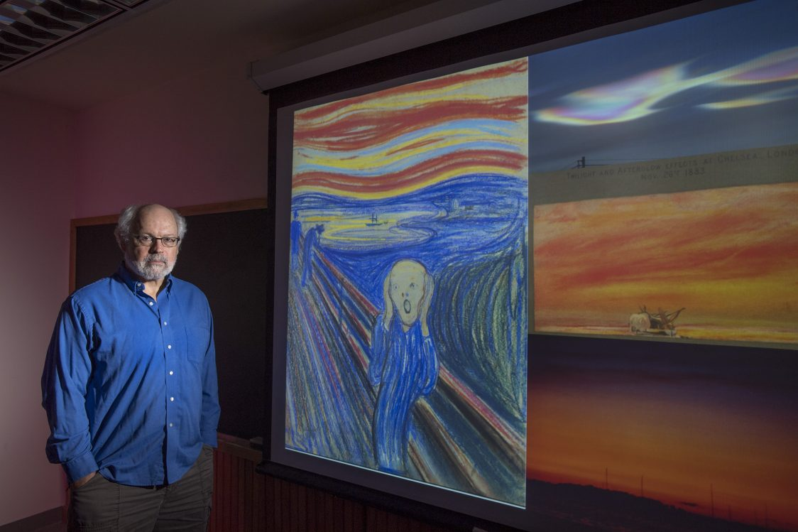 Rutgers Professor Alan Robock with an image of The Scream, an 1895 painting by Norwegian artist Edvard Munch. From top to bottom on the right are: a nacreous cloud over McMurdo Station in Antarctica in 2004; an 1883 drawing by William Ascroft showing the sky in London after the Krakatau eruption; and a 1982 volcanic sunset over Lake Mendota in Madison, Wisconsin, after the El Chichón eruption in Mexico. Photo: Nick Romanenko/Rutgers University