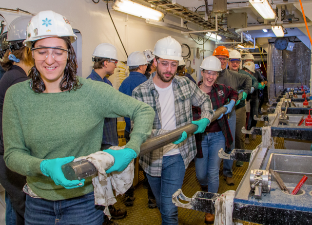 Samantha Bova leading the field team carrying a sediment core at sea.
